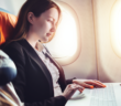 a female working on a laptop in an airplane
