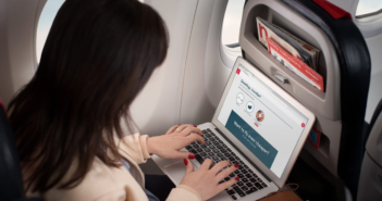 A Norwegian passenger accessing wi-fi on their laptop