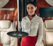 a crew member on a private jet holding a tray of champagne