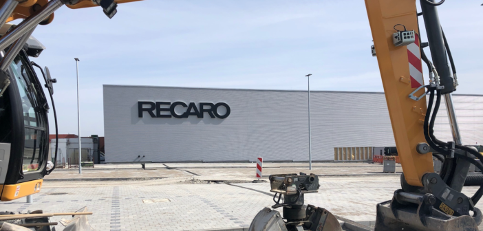 A digger in front of recaro's hq, being used to build an extension