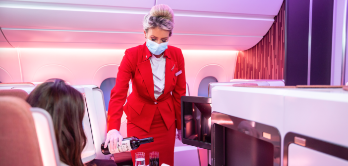 a stewardess in a virgin upper class cabin pouring wine for a guest