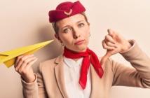 An air stewardess in airline uniform holding a paper plane and looking frustrated